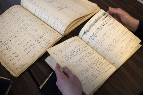 The Rev. Dave Young examines baptismal records at Immaculate Conception Church in Kenton, Ohio. Over the last decade, the church has hosted more funerals than baptisms.
