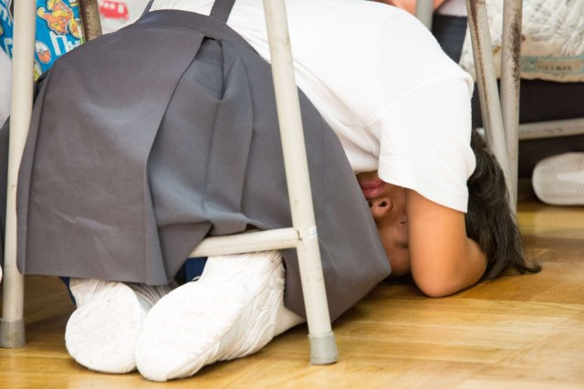 Students take cover under their desks during an evacuation drill in preparation for a North Korean missile attack, in Wajima, Ishikawa Prefecture, Japan, Aug. 30.