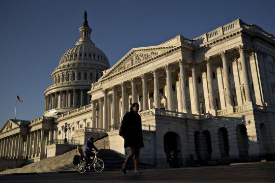 A pedestrian walks past the U.S. Capitol.