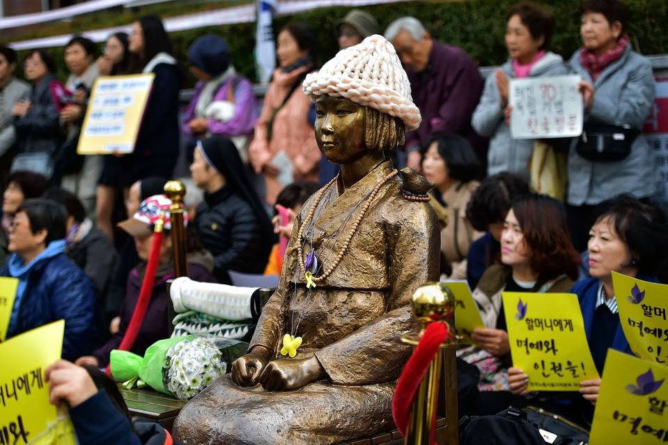 """Protesters sit next to a statue of a South Korean teenage girl in traditional costume, called the """"peace monument"""" for former """"comfort women,"""" during a demonstration near the Japanese embassy in Seoul on Nov. 11, 2015."""