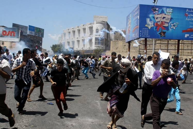 Anti-Houthi protesters run as pro-Houthi police troopers fire tear gas to disperse them in Yemen's southwestern city of Taiz on Sunday.