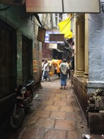 Bodies wrapped and being brought through the narrow streets
