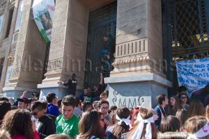 Il manifestante No Ponte mentre dà il via alla scalata ai cancelli.