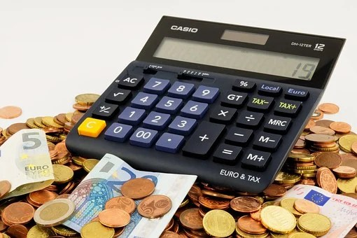 black calculator surrounded by coins and dollars