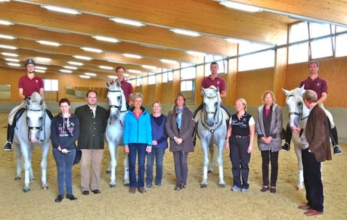 Suzie stands amongst Spanish Riding School riders and stallions in the indoor arena at Heldenberg with fellow students from Belgium, England, Norway, Germany and Austria.