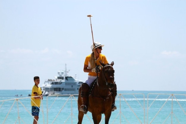 Kerstie playing beach polo while a yacht is anchored nearby. (Photo by Sheryel Aschfort, The Polo Papparazzi)