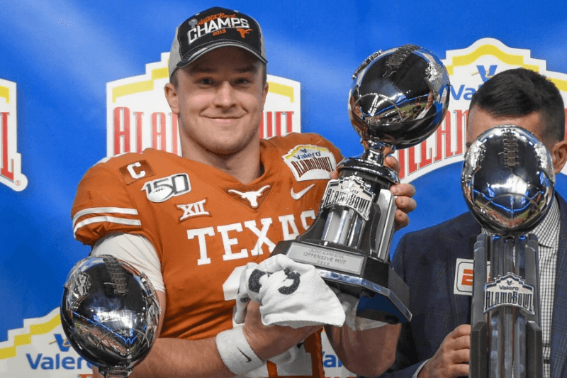 Texas Longhorns quarterback Sam Ehlinger (11) accepts the trophy for Offensive Player of the Game following the Alamo Bowl football game between the Utah Utes and Texas Longhorns at the Alamodome on December 31, 2019 in San Antonio, TX.