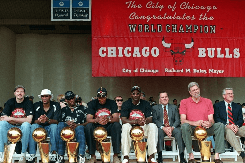 CHICAGO, IL - JUNE 16: From left, Chicago Bulls players Toni Kukoc, Ron Harper, Dennis Rodman, Scottie Pippen, and Michael Jordan sit with Chicago Mayor Richard Daley, Bulls head coach Phil Jackson and Illinois Governor Jim Edgar at the team's NBA championship rally in Chicago, IL 16 June. In the NBA Finals, the Bulls defeated the Utah Jazz four-games-to-two to win their third straight title and their sixth in eight years.