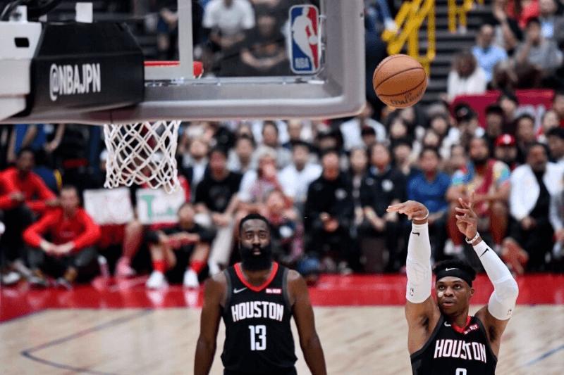 Houston Rockets guard Russell Westbrook (R) shoots a free throw as teammate James Harden looks on during the National Basketball Association (NBA) Japan Games 2019 pre-season basketball match between the Houston Rockets and Toronto Raptors in Saitama, a northern suburb of Tokyo on October 10, 2019.