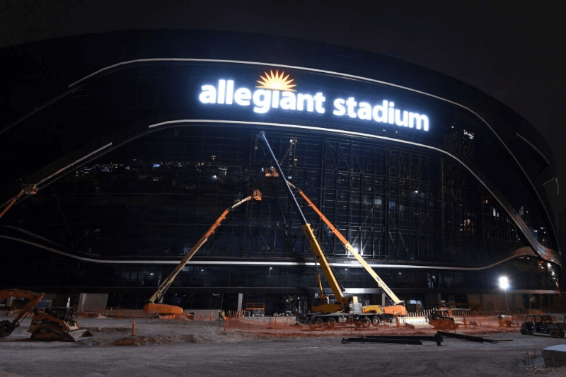 LAS VEGAS, NEVADA - APRIL 09: Workers test the lighting on an exterior sign at Allegiant Stadium for the first time as construction continues on the USD 2 billion, glass-domed future home of the Las Vegas Raiders on April 9, 2020 in Las Vegas, Nevada. The Raiders and the UNLV Rebels football teams are scheduled to begin play at the 65,000-seat facility in their 2020 seasons.