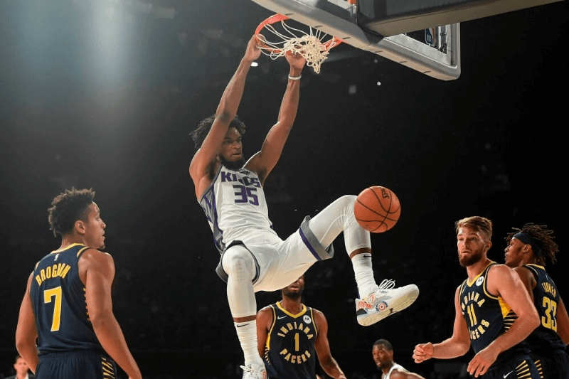Sacramento Kings player Marvin Bagley (C) shoots a ball as Indiana Pacers players Domantas Sabonis (2nd R) and Malcolm Brogdon (L) look on during the first pre-season NBA basketball game between Sacramento Kings and Indiana Pacers at the NSCI Dome in Mumbai on October 4, 2019.