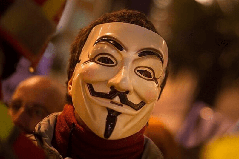 MADRID, SPAIN - FEBRUARY 23: A protestor wears a mask of 'Anonymous' the loosely associated hacking group during a march by thousands of people on February 23, 2013 in Madrid, Spain. Public health workers, civil servants and disaffected citizens converged on central Madrid to protest against the austerity measures of Prime Minister Mariano Rajoy.