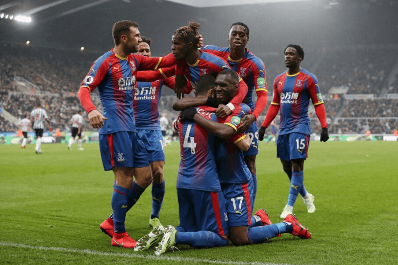 NEWCASTLE UPON TYNE, ENGLAND - APRIL 06: Luka Milivojevic of Crystal Palace celebrates after scoring his team's first goal from the penalty spot wit his team mates during the Premier League match between Newcastle United and Crystal Palace at St. James Park on April 06, 2019 in Newcastle upon Tyne, United Kingdom.
