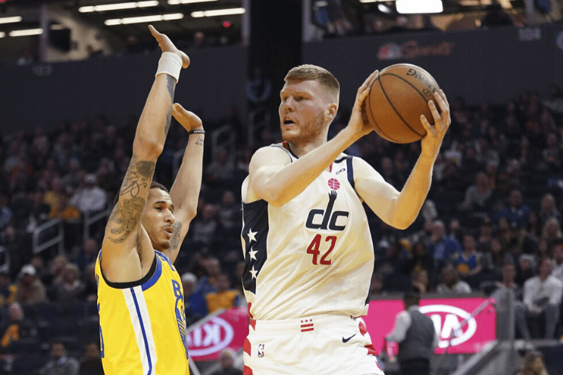 March 1, 2020; San Francisco, California, USA; Washington Wizards forward Davis Bertans (42) passes the basketball against Golden State Warriors forward Juan Toscano-Anderson (95) during the second quarter at Chase Center.
