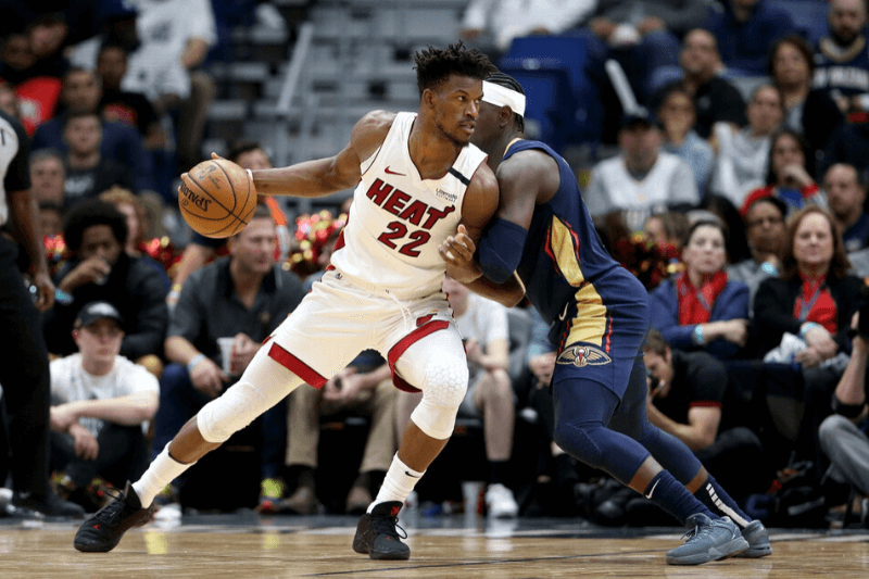 Mar 6, 2020; New Orleans, Louisiana, USA; Miami Heat forward Jimmy Butler (22) drives against New Orleans Pelicans guard Jrue Holiday (11) in the second half at the Smoothie King Center.