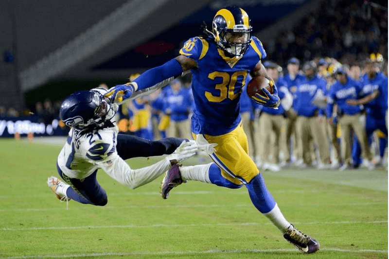 LOS ANGELES, CALIFORNIA - DECEMBER 08: Running back Todd Gurley #30 of the Los Angeles Rams stiff arms cornerback Tre Flowers #21 of the Seattle Seahawks on his way to a touchdown in the fourth quarter of the game at Los Angeles Memorial Coliseum on December 08, 2019 in Los Angeles, California.