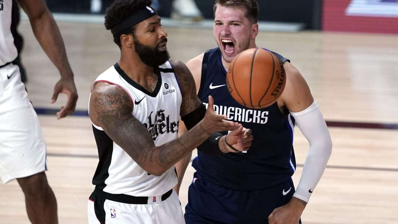 Aug 23, 2020; Lake Buena Vista, Florida, USA; Dallas Mavericks' Luka Doncic, right, reacts after making a basket as Los Angeles Clippers' Marcus Morris Sr. (31) reaches for the ball during the second half of an NBA basketball first round playoff game at AdventHealth Arena. Mandatory Credit: Ashley Landis/Pool Photo-USA TODAY Sports