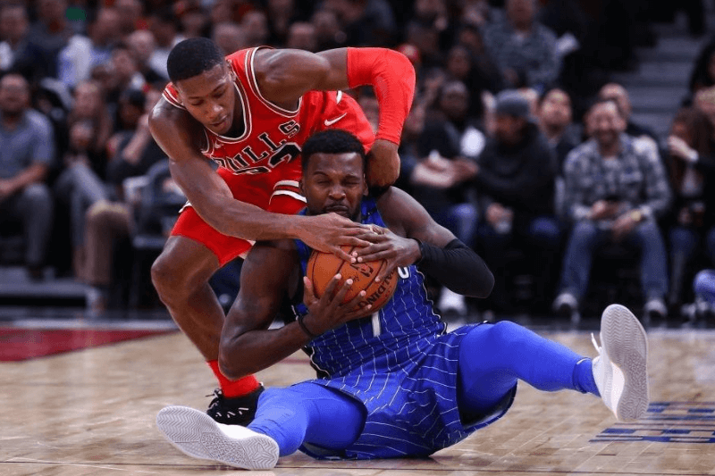 CHICAGO, USA - DECEMBER 20: Kris Dunn (32) of Chicago Bulls competes with Shelvin Mack (7) of Orlando Magic during an NBA basketball match between Chicago Bulls and Orlando Magic at United Center in Chicago, Illinois, United States on December 20, 2017.
