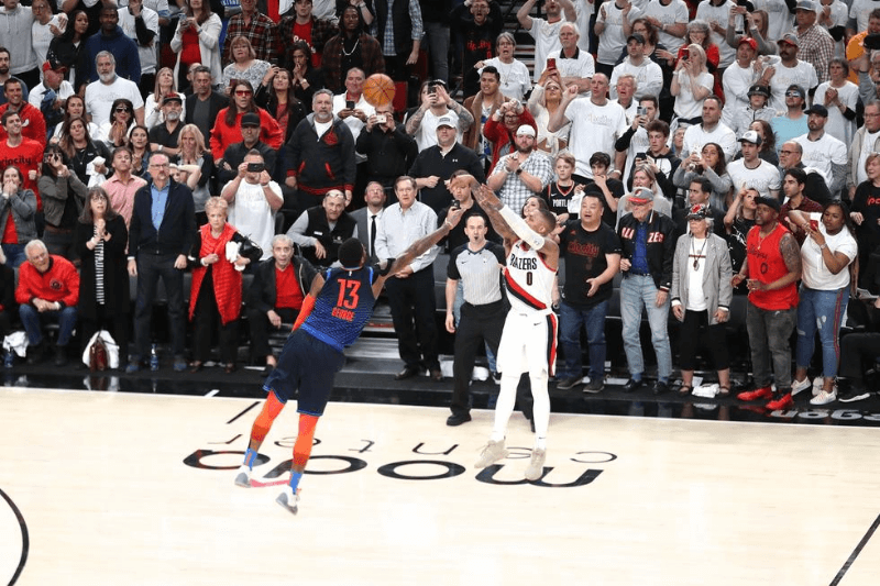 Apr 23, 2019; Portland, OR, USA; Portland Trail Blazers guard Damian Lillard (0) makes a three-point shot over Oklahoma City Thunder forward Paul George (13) to defeat Oklahoma City Thunder 118-115 in game five of the first round of the 2019 NBA Playoffs at Moda Center.