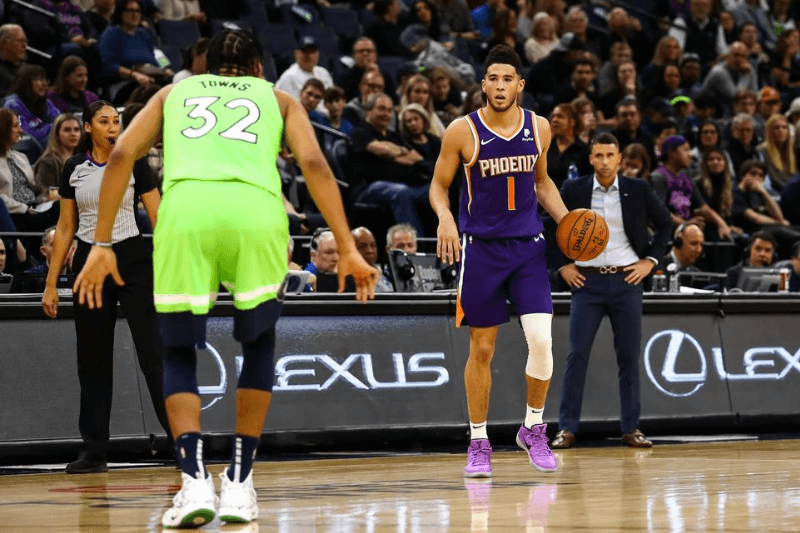 Nov 23, 2019; Minneapolis, MN, USA; Phoenix Suns guard Devin Booker (1) dribbles the ball against Minnesota Timberwolves center Karl-Anthony Towns (32) in the third quarter at Target Center.