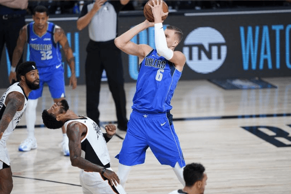 Aug 21, 2020; Lake Buena Vista, Florida, USA; Los Angeles Clippers' Paul George falls back after colliding with Dallas Mavericks' Kristaps Porzingis (6) during the second half in a NBA basketball first round playoff game at AdventHealth Arena