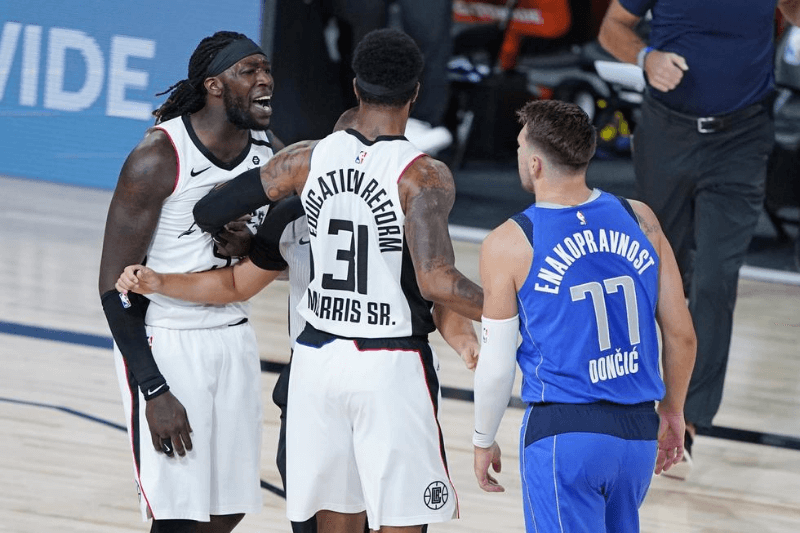Aug 21, 2020; Lake Buena Vista, Florida, USA; Los Angeles Clippers' Marcus Morris Sr. (31) gets between Montrezl Harrell, left, and Dallas Mavericks' Luka Doncic (77) during the first half in a NBA basketball first round playoff game at AdventHealth Arena.