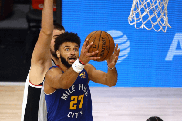 Sep 11, 2020; Lake Buena Vista, Florida, USA; Denver Nuggets guard Jamal Murray (27) makes a basket over LA Clippers forward Marcus Morris Sr. (31) and forward Kawhi Leonard (2) during the first half of game five in the second round of the 2020 NBA Playoffs at ESPN Wide World of Sports Complex. Mandatory Credit: Kim Klement-USA TODAY Sports