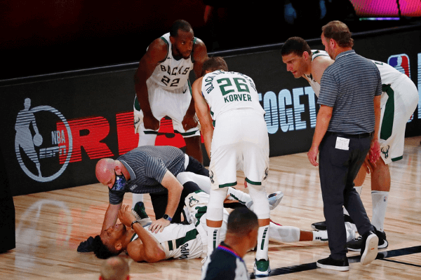 Sep 6, 2020; Lake Buena Vista, Florida, USA; Milwaukee Bucks forward Giannis Antetokounmpo (34) is assessed after an apparent injury during the first half of game four of the second round of the 2020 NBA Playoffs against the Miami Heat at ESPN Wide World of Sports Complex