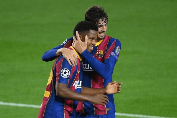Barcelona's Spanish forward Ansu Fati (L) celebrates with Barcelona's Portuguese forward Francisco Trincao after scoring a goal during the UEFA Champions League football match between FC Barcelona and Ferencvarosi TC at the Camp Nou stadium in Barcelona on October 20, 2020. (Photo by LLUIS GENE / AFP) (Photo by LLUIS GENE/AFP via Getty Images)