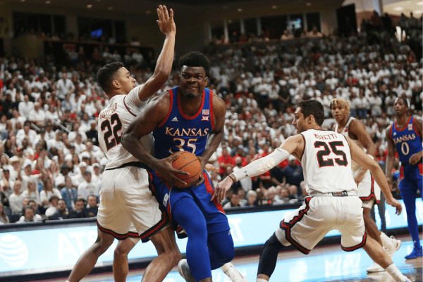 Mar 7, 2020; Lubbock, Texas, USA; Kansas Jayhawks froward Udoka Azubuike (35) is pinned under the basket by Texas Tech Red Raiders forward TJ Holyfield (22) in the first half at United Supermarkets Arena.