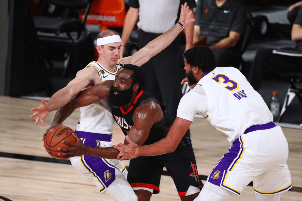 Sep 8, 2020; Lake Buena Vista, Florida, USA; Houston Rockets guard James Harden (middle) tries to pass the ball against Los Angeles Lakers guard Alex Caruso (left) and forward Anthony Davis (3) during the first half of game three in the second round of the 2020 NBA Playoffs at AdventHealth Arena.