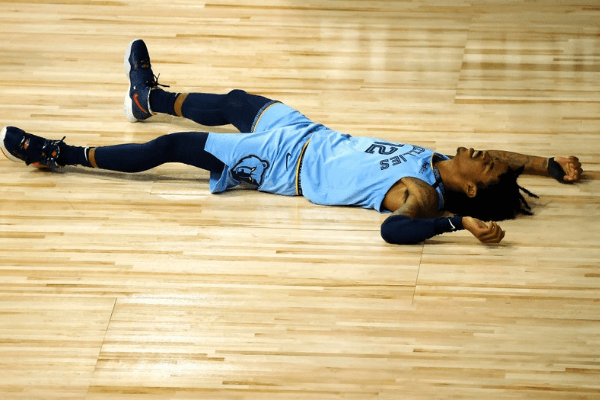 Ja Morant #12 of the Memphis Grizzlies lays on the ground after he was fouled by the Portland Trail Blazers during the third quarter in the Western Conference play-in game one at The Field House at ESPN Wide World Of Sports Complex on August 15, 2020 in Lake Buena Vista, Florida.
