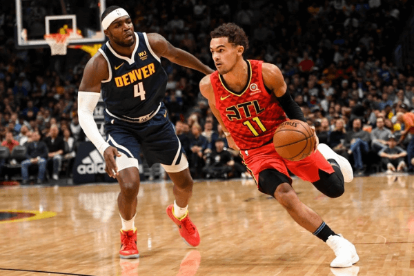 Trae Young (11) of the Atlanta Hawks drives on Paul Millsap (4) of the Denver Nuggets during the third quarter on Tuesday, November 12, 2019.
