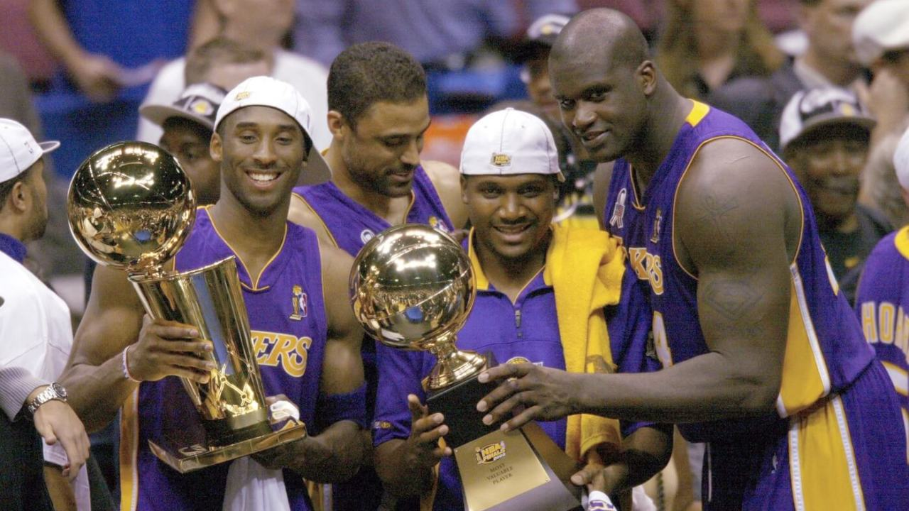June 12, 2002; East Rutherford, NJ, USA; (left to right) Los Angeles Lakers Kobe Bryant, Lindsay Hunter and Shaquille O'Neal hold championship trophies after winning Game 4 of the NBA Finals at The Meadowlands. Mandatory Credit: Robert Deutsch-USA TODAY Sports