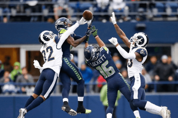 Cornerback Troy Hill #32 of the Los Angeles Rams knocks away a pass as wide receiver Paul Richardson #10 of the Seattle Seahawks and Tyler Lockett #16 try to make the completion during the 2nd quarter of the game at CenturyLink Field on December 17, 2017 in Seattle, Washington.