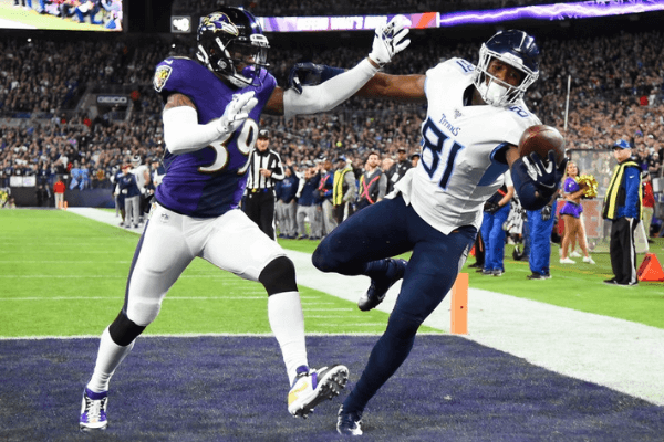 Jonnu Smith #81 of the Tennessee Titans catches a touchdown over Brandon Carr #39 of the Baltimore Ravens in the first quarter of the AFC Divisional Playoff game at M&T Bank Stadium on January 11, 2020 in Baltimore, Maryland.