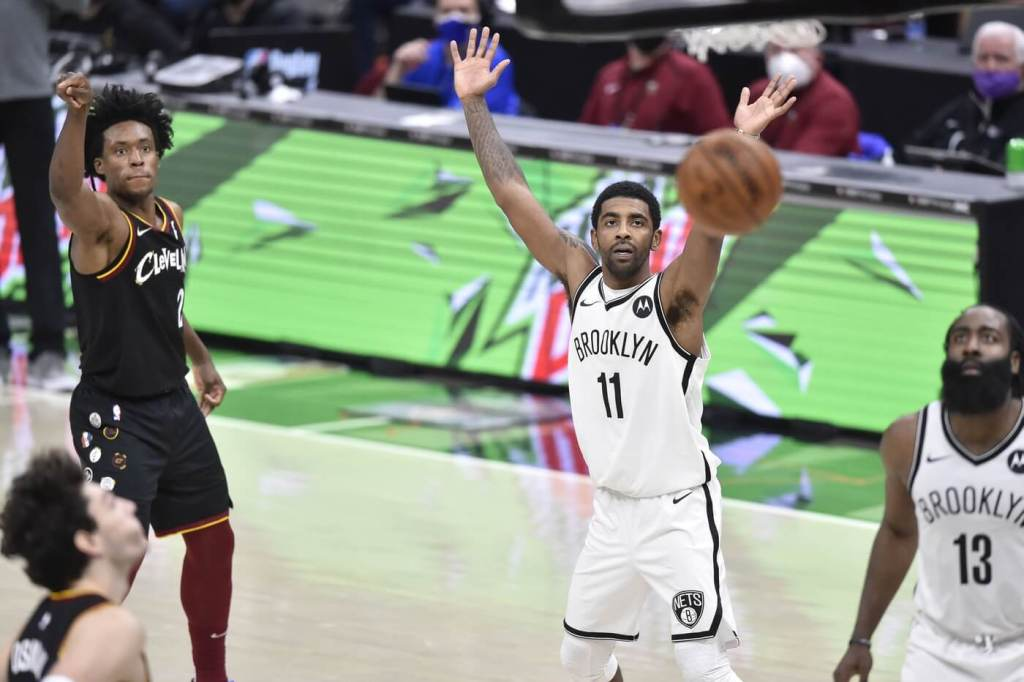 Jan 20, 2021; Cleveland, Ohio, USA; Brooklyn Nets guard Kyrie Irving (11) and guard James Harden (13) watch as Cleveland Cavaliers guard Collin Sexton (2) makes a three-point basket at the end of the first overtime at Rocket Mortgage FieldHouse. Mandatory Credit: David Richard-USA TODAY Sports