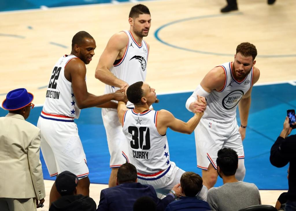 Feb 17, 2019; Charlotte, NC, USA; Team Giannis guard Stephen Curry of the Golden State Warriors (30) is picked up by teammates forward Khris Middleton of the Milwaukee Bucks (22) and forward Blake Griffin of the Detroit Pistons (23) during the All Star Game at Spectrum Center. Mandatory Credit: Jeremy Brevard-USA TODAY Sports