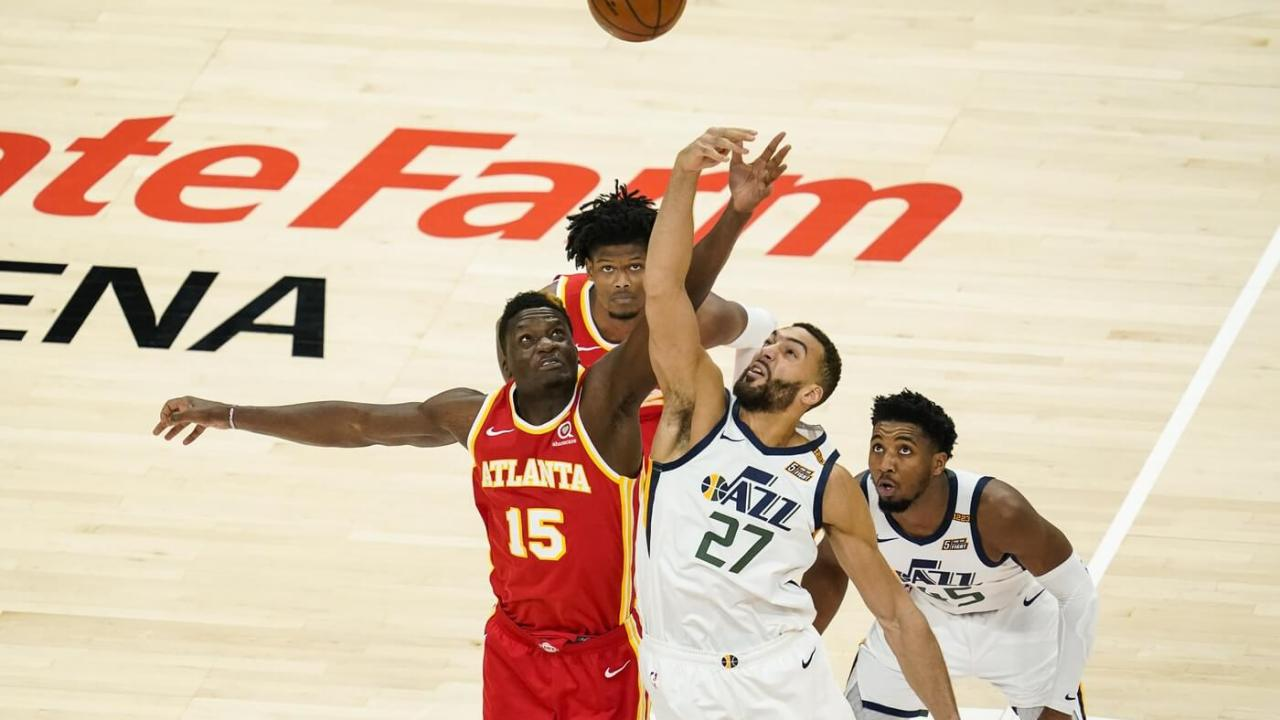 Atlanta Hawks center Clint Capela (15) and Utah Jazz center Rudy Gobert (27) battle for the opening tip during the first quarter at State Farm Arena.