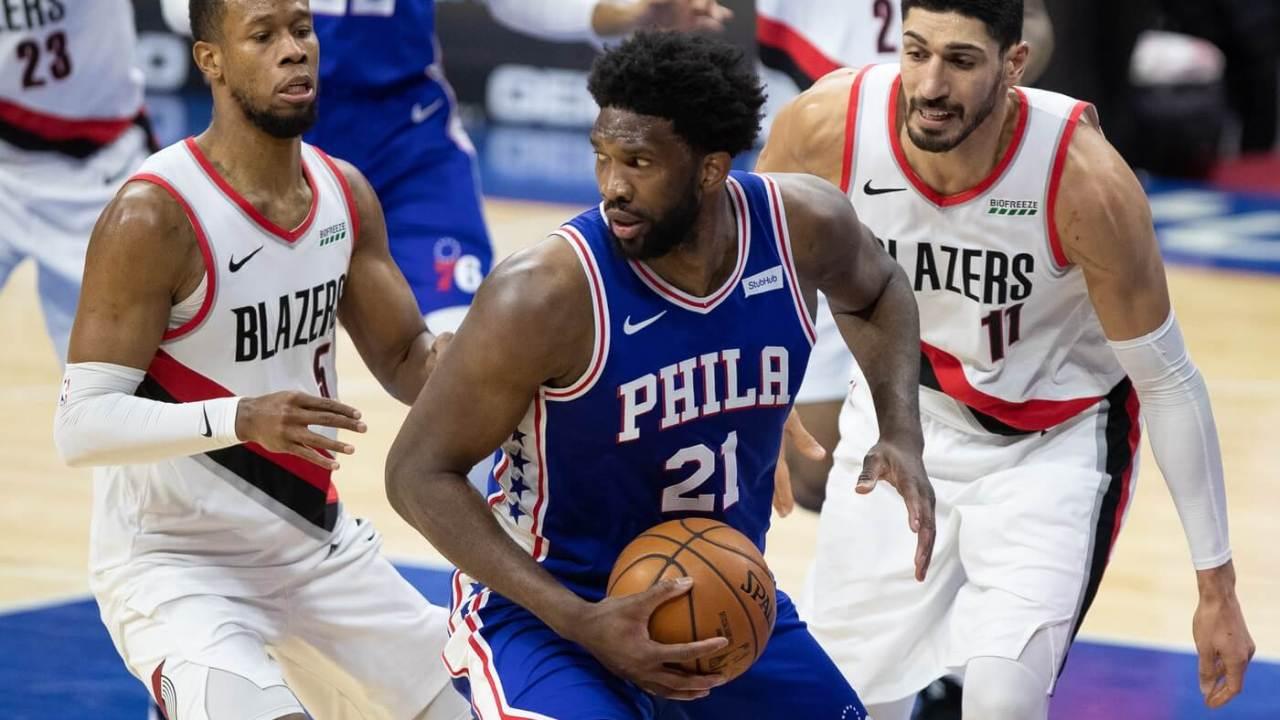 Philadelphia 76ers center Joel Embiid (21) controls the ball against Portland Trail Blazers guard Rodney Hood (5) and center Enes Kanter (11) during the third quarter at Wells Fargo Center.
