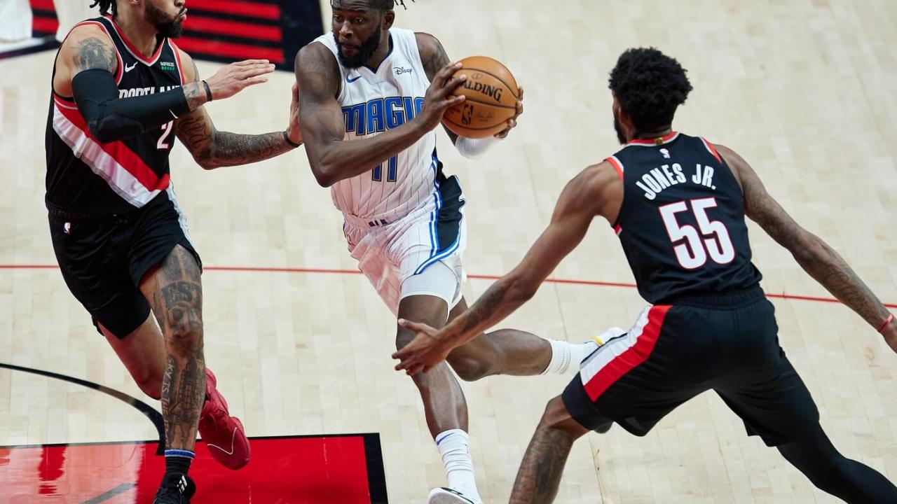 Orlando Magic forward James Ennis III (11) drives to the basket between Portland Trail Blazers guard Gary Trent Jr. (2) and forward Derrick Jones Jr. (55) during the third quarter at the Moda Center.