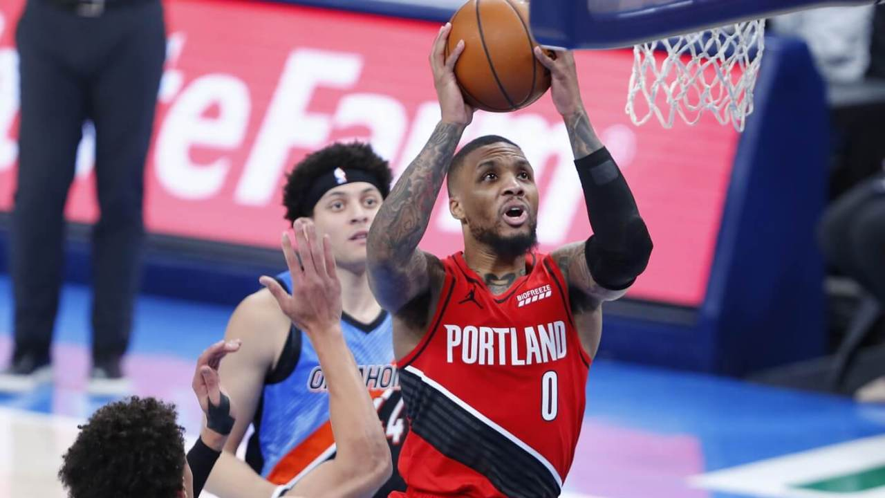 Portland Trail Blazers guard Damian Lillard (0) drives to the basket against Oklahoma City Thunder center Isaiah Roby (left) and forward Justin Jackson (background) during the second half at Chesapeake Energy Arena.