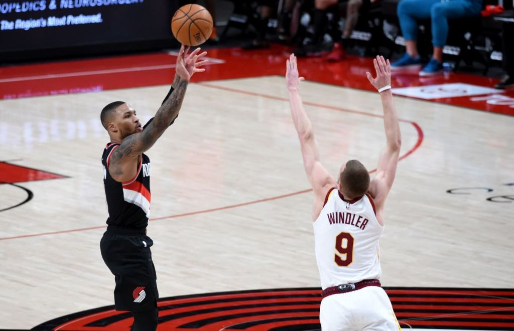 Feb 12, 2021; Portland, Oregon, USA; Portland Trail Blazers guard Damian Lillard (0) hits a shot over Cleveland Cavaliers guard Dylan Windler (9) during the second half of the game at Moda Center. Mandatory Credit: Steve Dykes-USA TODAY Sports