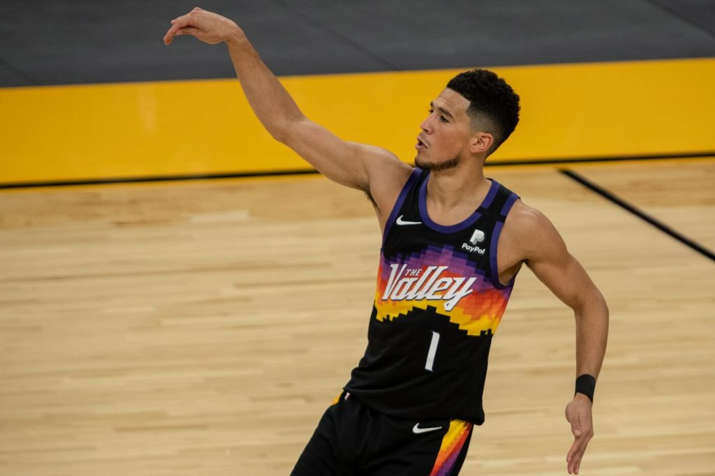 Feb 14, 2021; Phoenix, Arizona, USA; Phoenix Suns guard Devin Booker (1) shoots the ball against the Orlando Magic during the first half at Phoenix Suns Arena. Mandatory Credit: Jennifer Stewart-USA TODAY Sports
