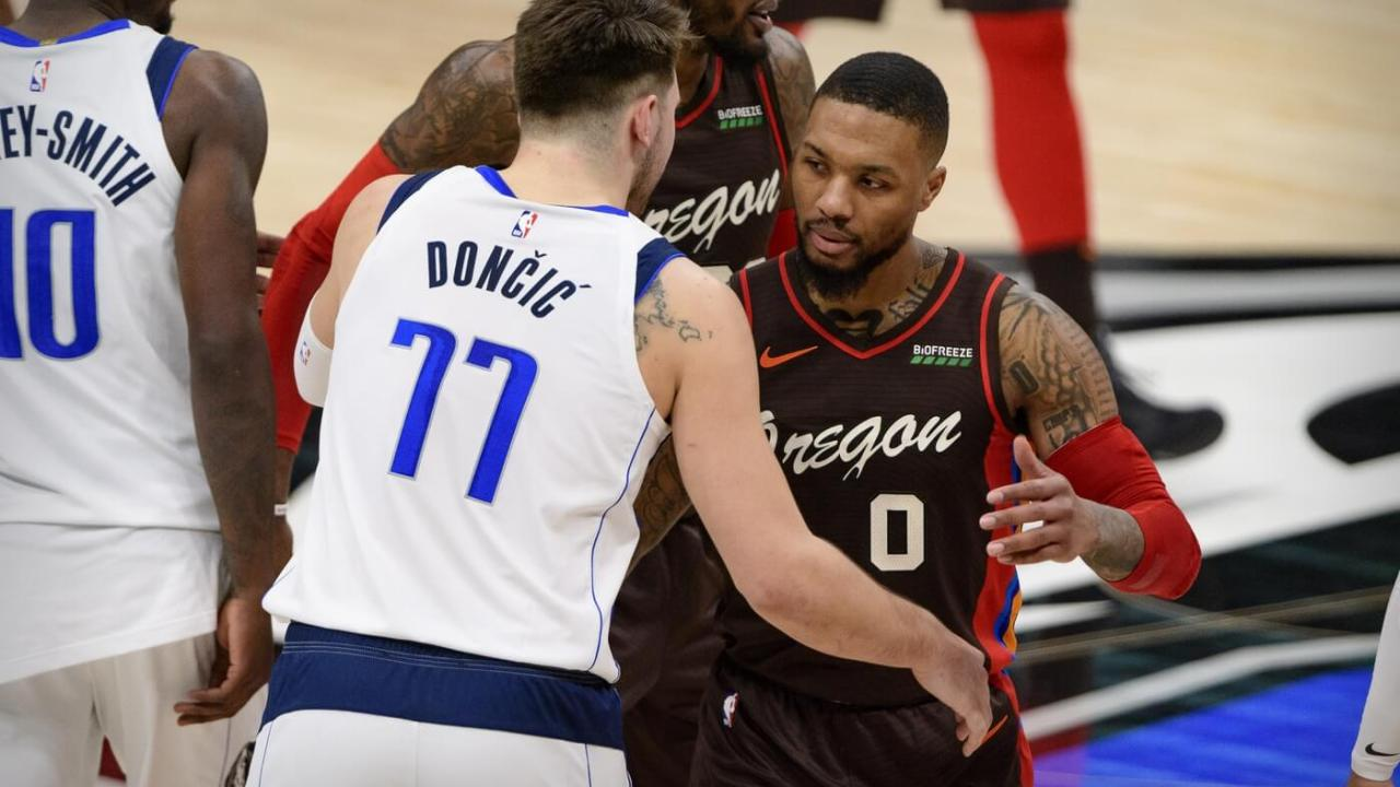 Feb 14, 2021; Dallas, Texas, USA; Dallas Mavericks guard Luka Doncic (77) hugs Portland Trail Blazers guard Damian Lillard (0) after the game at the American Airlines Center. Mandatory Credit: Jerome Miron-USA TODAY Sports