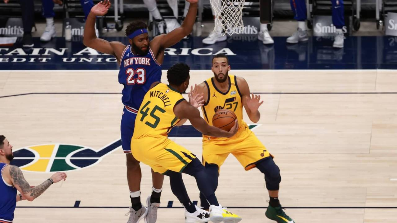 Jan 26, 2021; Salt Lake City, Utah, USA; Utah Jazz guard Donovan Mitchell (45) pass the ball under the arms of New York Knicks center Mitchell Robinson (23) to center Rudy Gobert (27) during the fourth quarter at Vivint Smart Home Arena. Utah Jazz wins 108-94. Mandatory Credit: Chris Nicoll-USA TODAY Sports