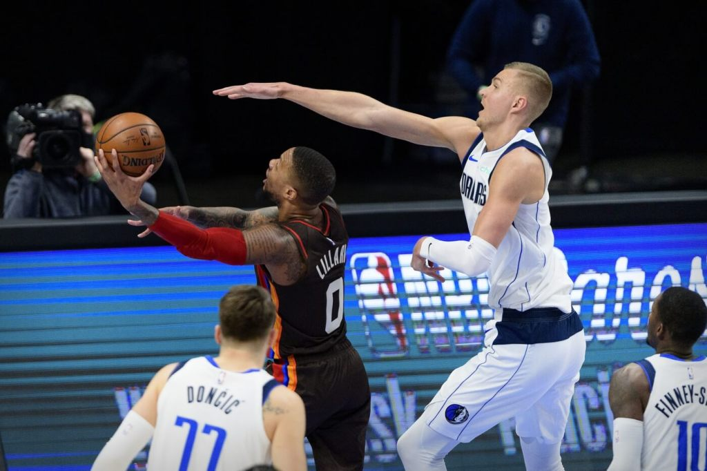 Feb 14, 2021; Dallas, Texas, USA; Portland Trail Blazers guard Damian Lillard (0) and Dallas Mavericks center Kristaps Porzingis (6) in action during the game between the Dallas Mavericks and the Portland Trail Blazers at the American Airlines Center. Mandatory Credit: Jerome Miron-USA TODAY Sports
