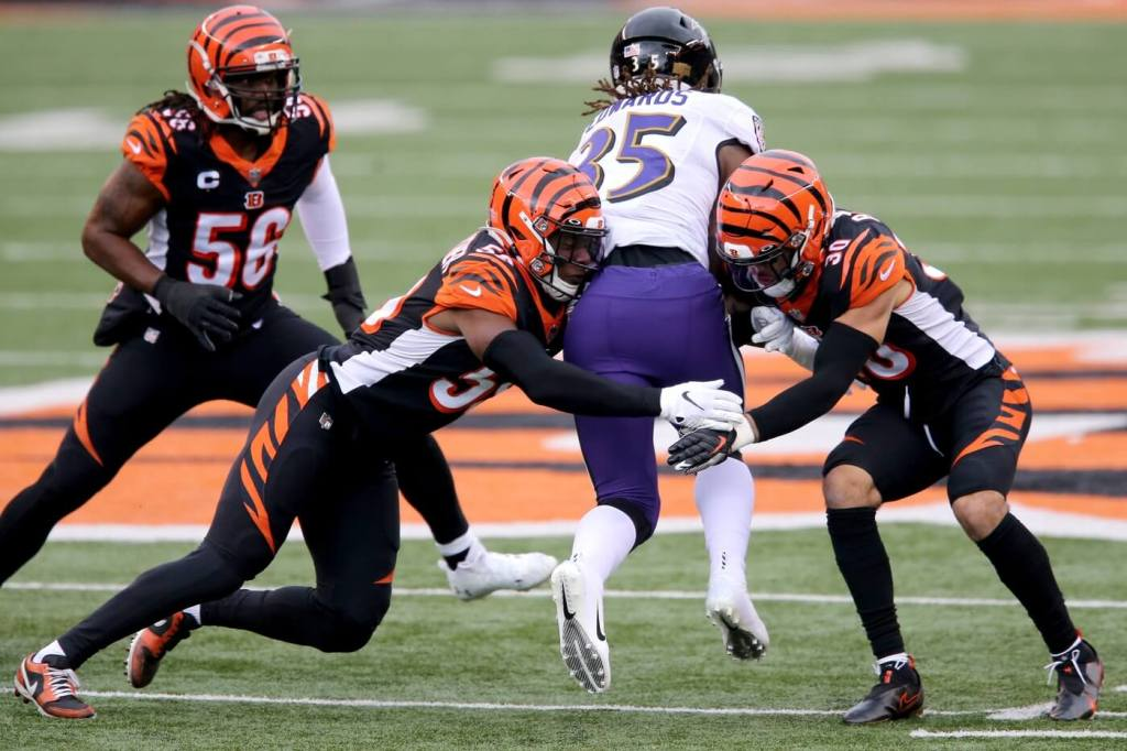 Cincinnati Bengals defensive end Carl Lawson (58) and Cincinnati Bengals free safety Jessie Bates (30) combine to tackle Baltimore Ravens cornerback Tavon Young (25) in the first quarter during a Week 17 NFL football game