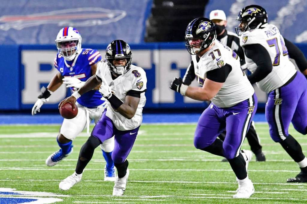 Baltimore Ravens quarterback Lamar Jackson (8) runs with the ball against the Baltimore Ravens during the second half of an AFC Divisional Round playoff game at Bills Stadium.