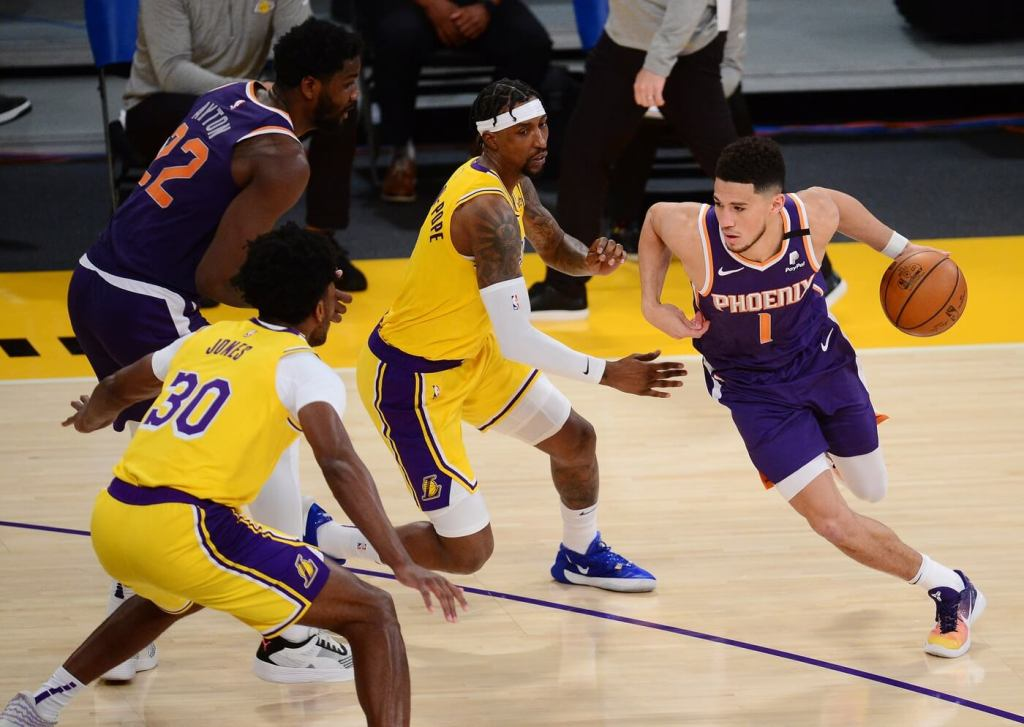 Phoenix Suns guard Devin Booker (1) moves the ball against Los Angeles Lakers guard Kentavious Caldwell-Pope (1) and center Damian Jones (30) during the first half at Staples Center.